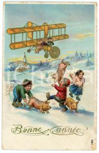1911 BONNE ANNÉE Children catching pigs thrown from a plane *DAMAGED postcard